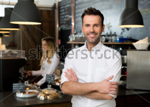 stock-photo-successful-small-business-owner-standing-with-crossed-arms-with-employee-in-background-preparing-286965218